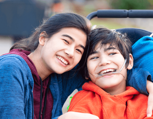 Image of a young disabled boy smiling with sister