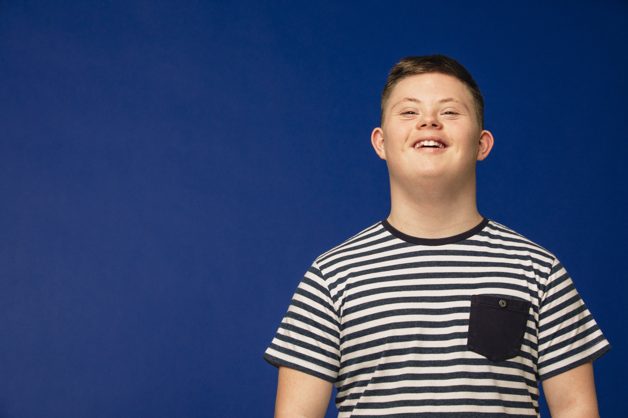Image of a teenage down syndrome boy looking at the camera, smiling and looking happy